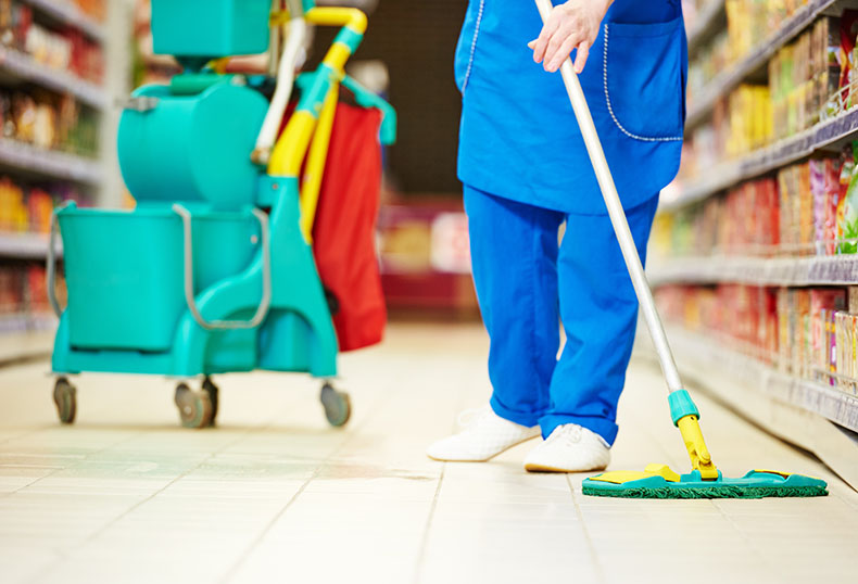 Female cleaner worker in uniform with mop cleaning the floor of supermarket shop store